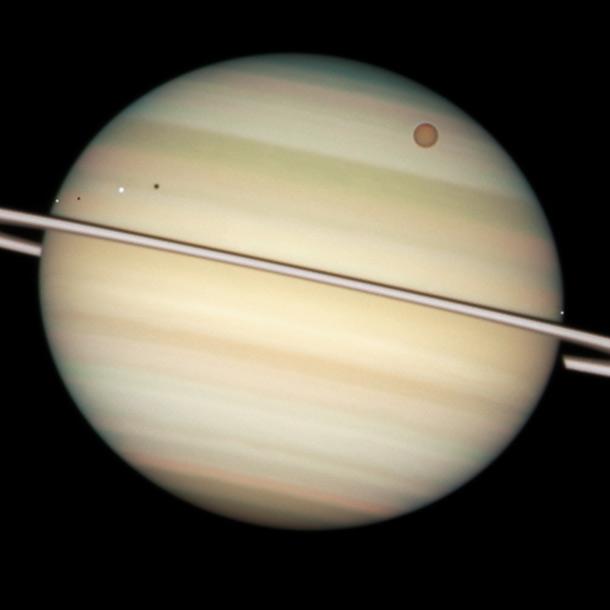 Nej, det ser ikke sådan ud i min kikkert; men man *kan* se planeten og ringene. Månerne kan kun ses som lysende pletter; men man kan SE DET :-)