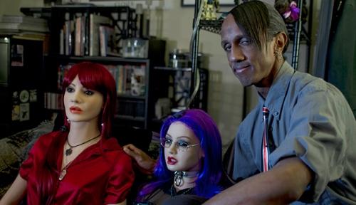 Det er *ikke* fra en film, han ser sådan ud i virkeligheden og de 2 dukker er hans koner. WTF?